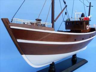 This wooden fishing boat model is attached to a sturdy wooden base
